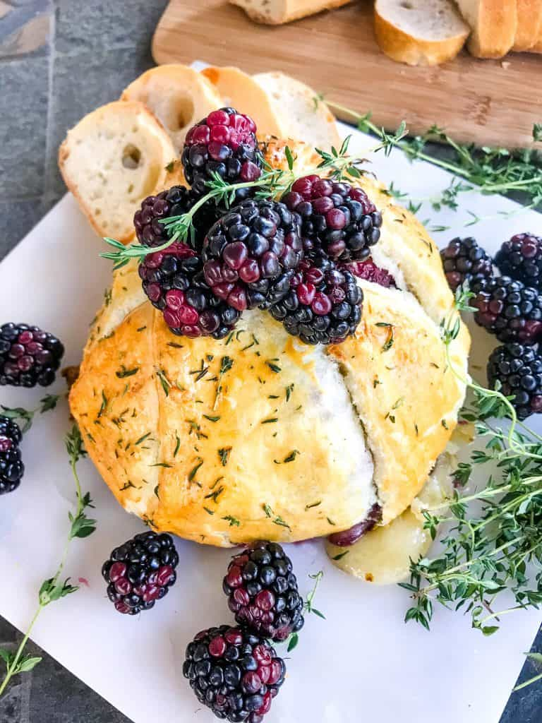 A full Thyme Blackberry Baked Brie in Puff Pastry on a marble board surrounded by thyme and berries