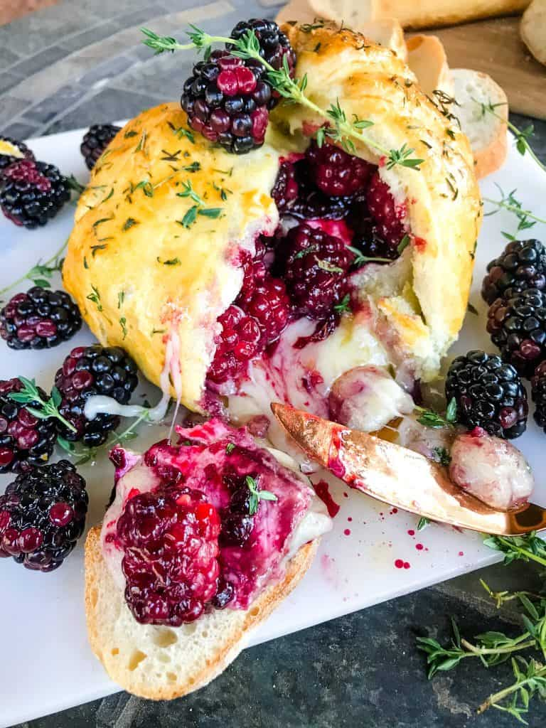 Thyme Blackberry Baked Brie in Puff Pastry cut open with cheese oozing out surrounded by berries and crostini