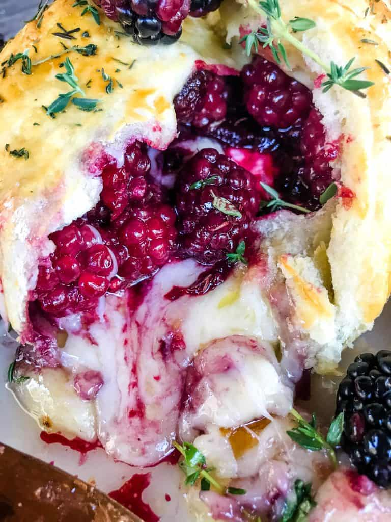 A close up of Thyme Blackberry Baked Brie in Puff Pastry cut open with berries and cheese oozing out