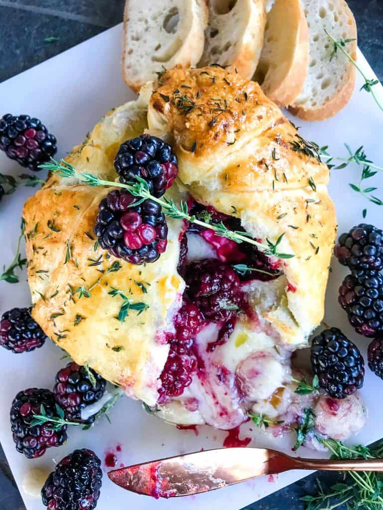 A Thyme Blackberry Baked Brie in Puff Pastry cut open with cheese oozing out on a marble board