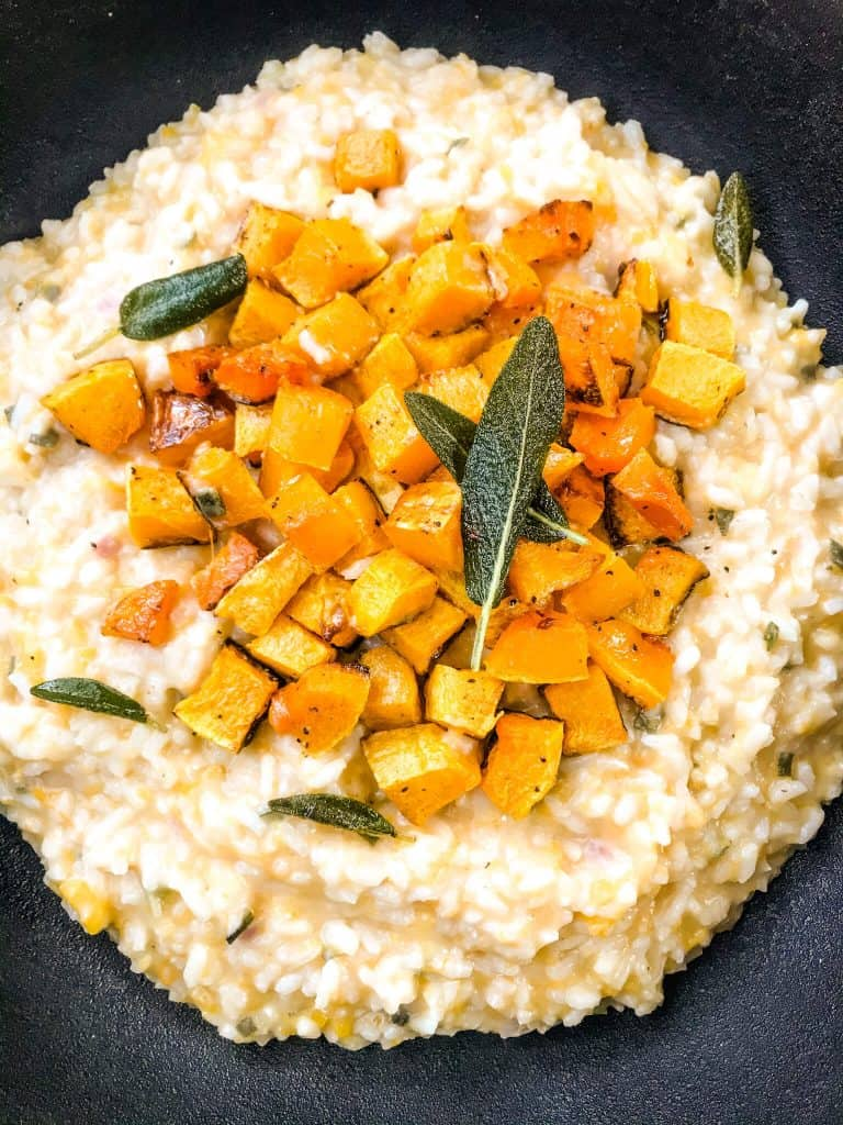 A black bowl filled with Butternut Squash Sage Risotto and topped with sage leaves and squash cubes.