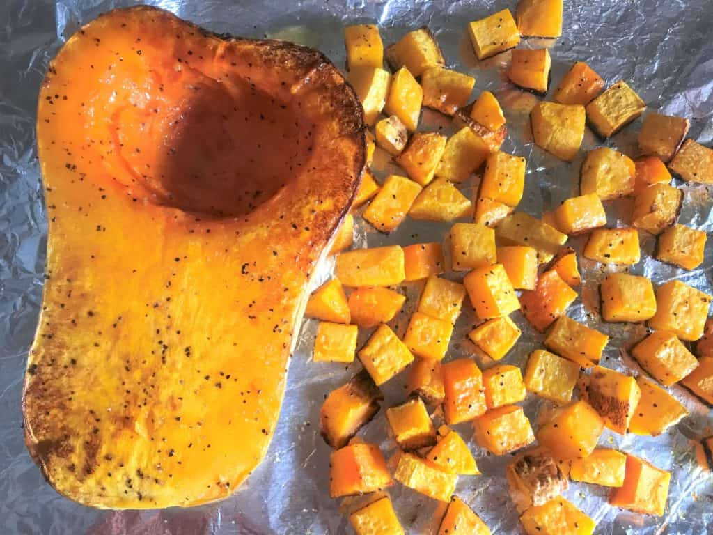 Squash being roasted on a baking sheet