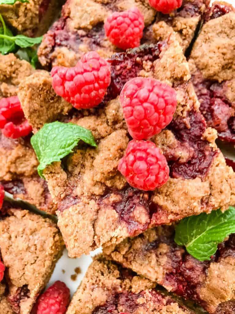 A close up of one Chocolate Raspberry Crumble Bar with fresh raspberries