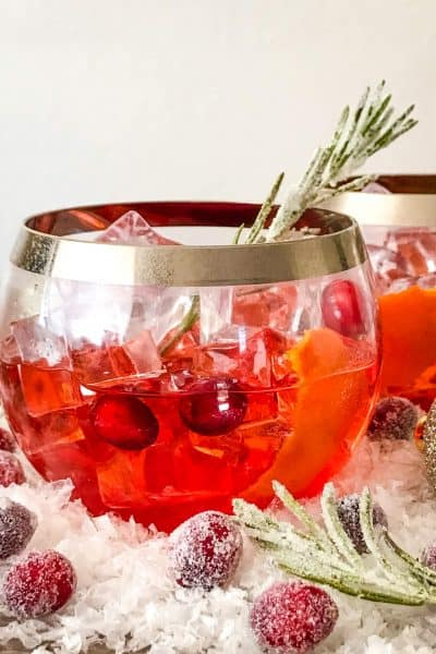 A glass of Cranberry Old Fashioned Cocktail with cranberries and rosemary in and around it