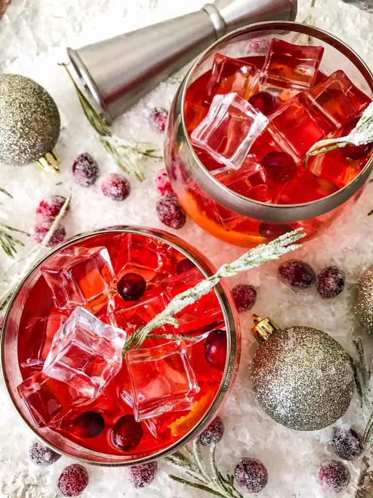 Top view of two glasses of Cranberry Old Fashioned Cocktail surrounded by cranberries on white snow
