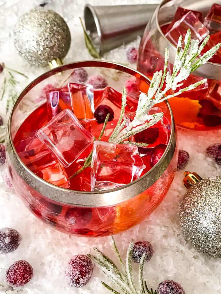 Top view of red cocktail with rosemary and cranberries in it