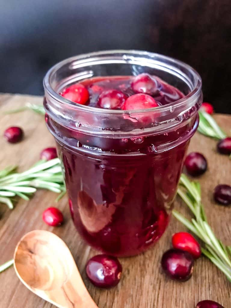 A jar of Cranberry Simple Syrup surrounded by cranberries