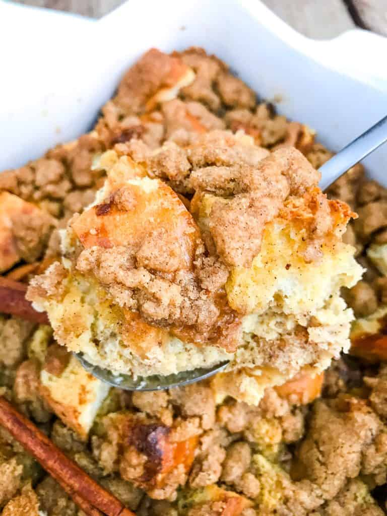A spoon scooping Overnight Eggnog French Toast Casserole out of the dish