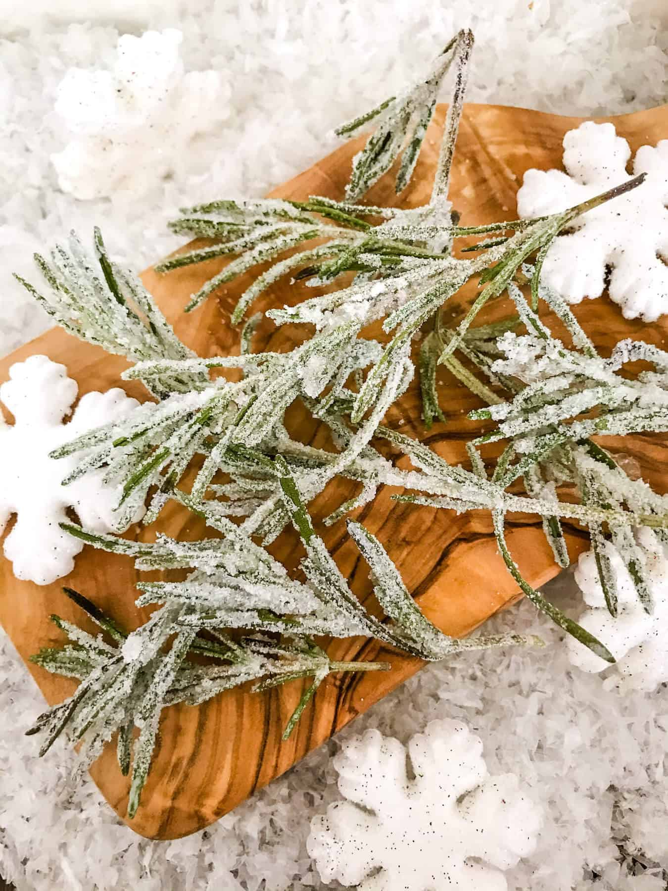 Frosted herbs with snow around it on a cutting board