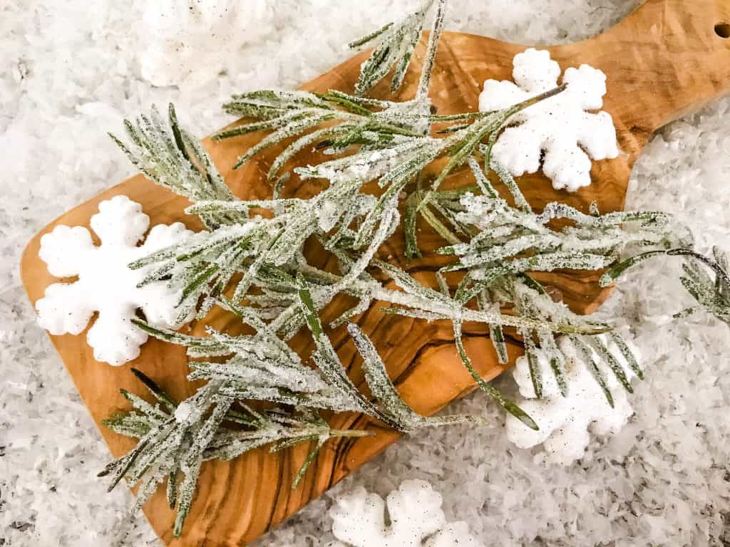 Sparkling Rosemary (Sugared Rosemary) on a cutting board with snow around it