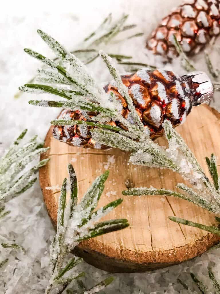 Sparkling Rosemary (Sugared Rosemary) on a slice of wood with a pinecone ornament