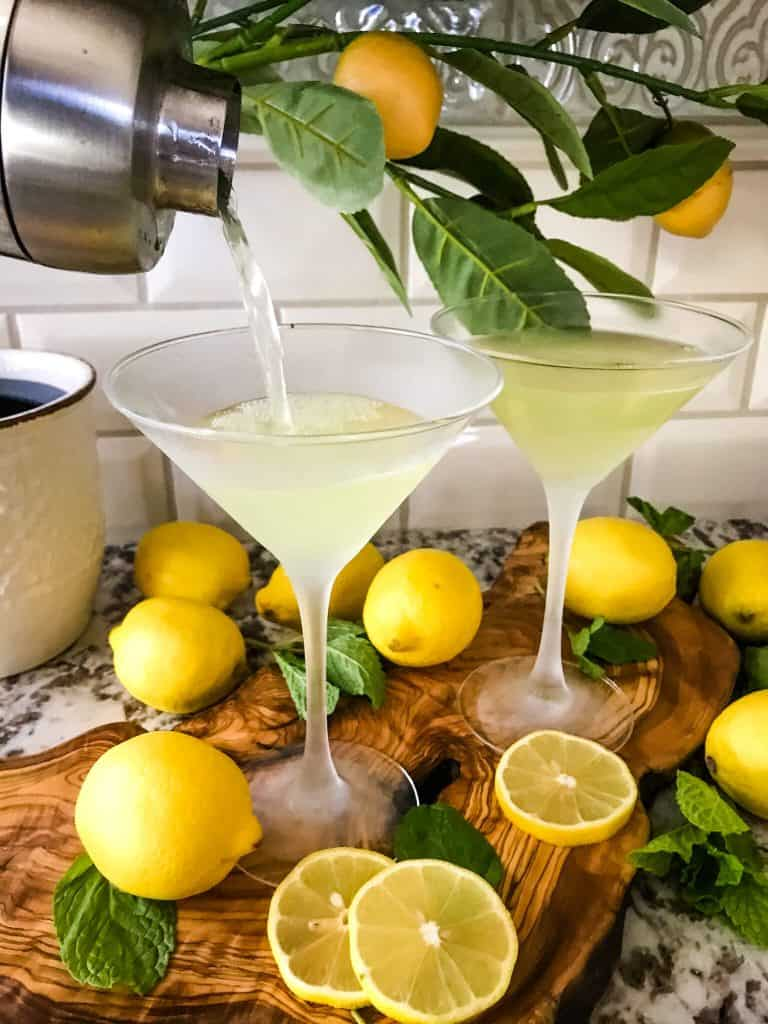 A cocktail shaker pouring a light yellow cocktail into glasses