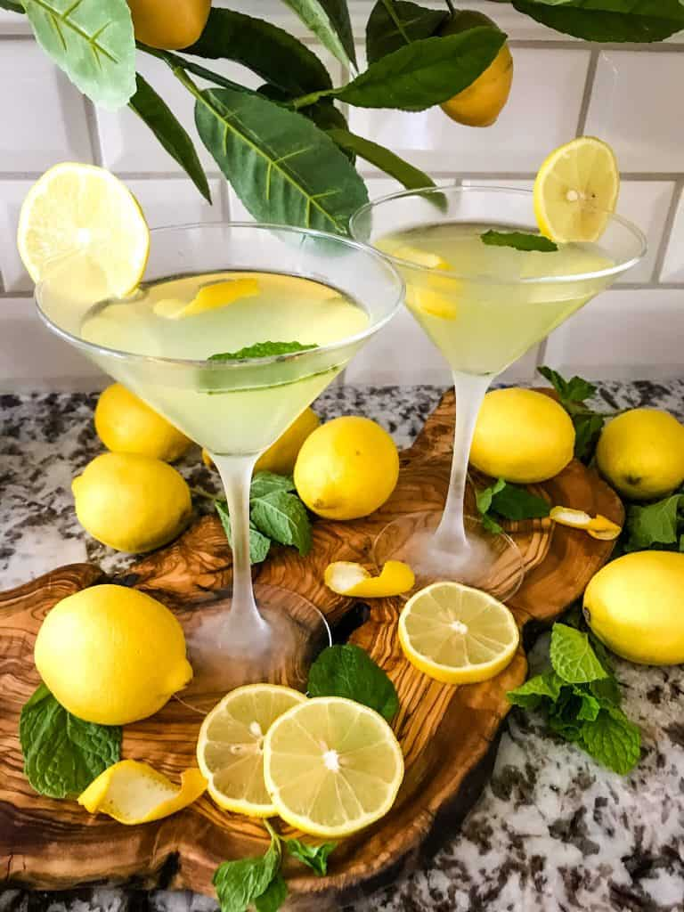 Italian lemon cocktails with lemons around them on a wood board