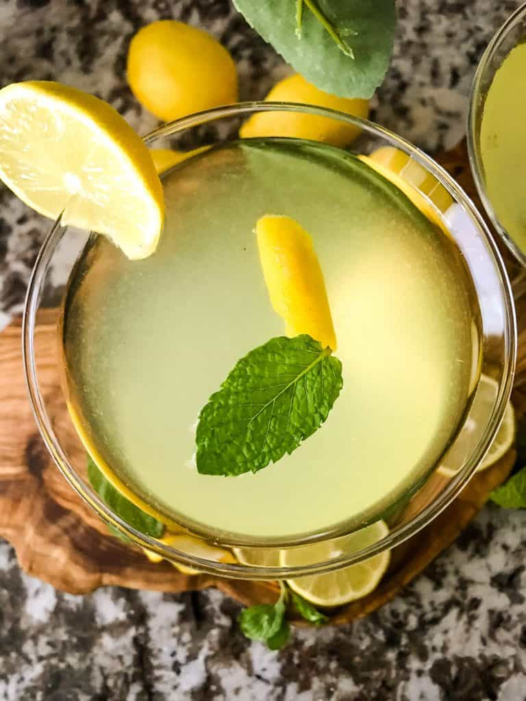 Top view of a martini with lemon and mint floating in it