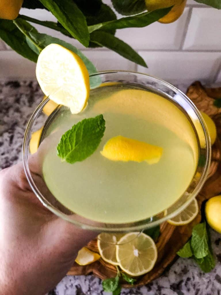 A hand holding a lemon martini with view from the top