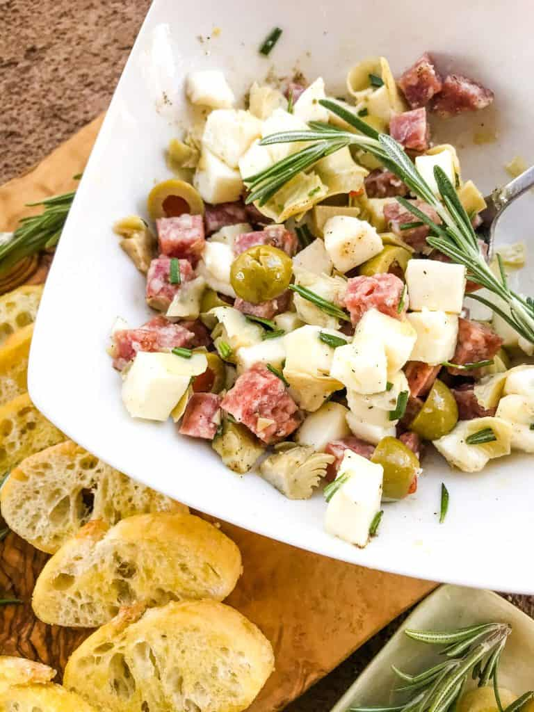 A bowl of salami, cheese, olives, and artichokes with bread slices next to it