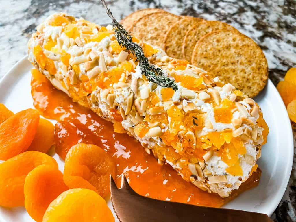 Apricot Almond Goat Cheese Log on top of jam on a plate with crackers and more dried apricots
