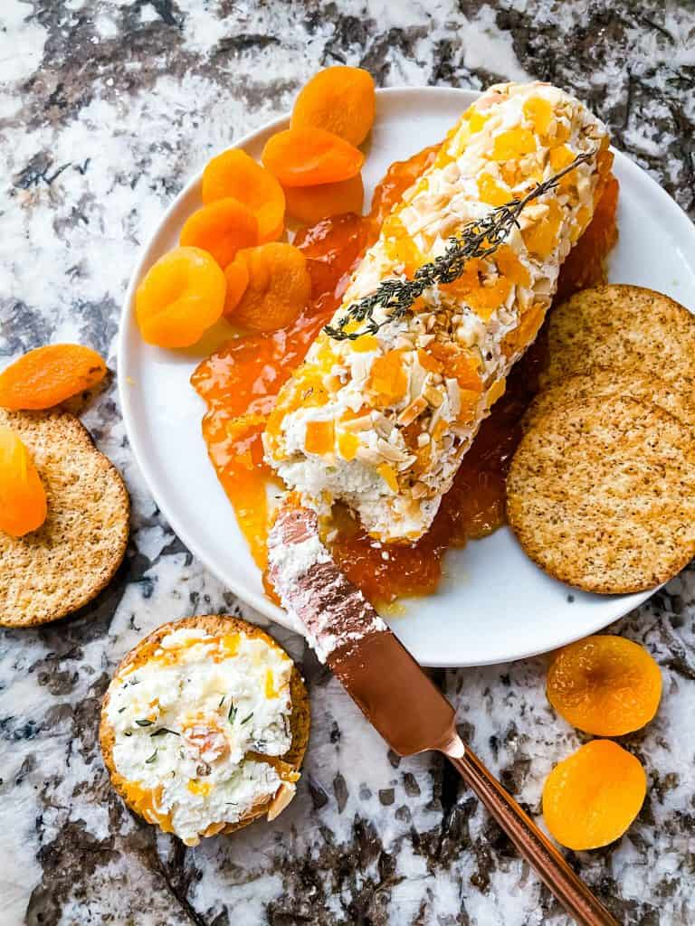 Apricot Almond Goat Cheese Log sliced into with some cheese on a cracker