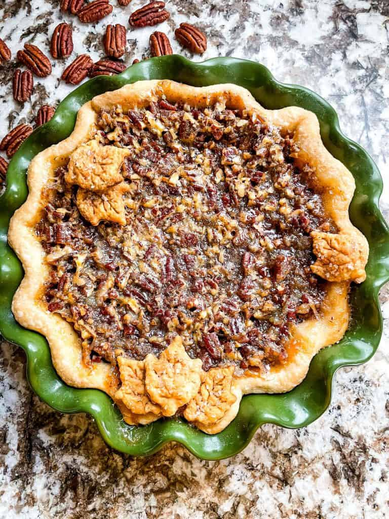A full Chocolate Bourbon Pecan Pie in a green pie dish from the top