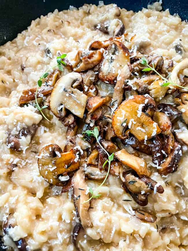 Close up of Creamy Mushroom Risotto in a black bowl topped with mushrooms