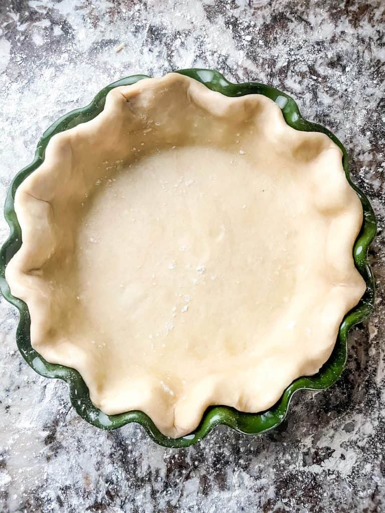 Easy Pie Crust (Food Processor) in a green pie dish from the top on a granite counter