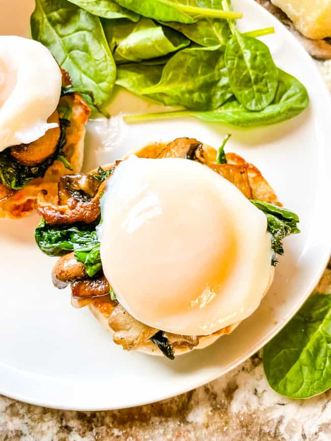 A poached egg on top of eggs benedict stack