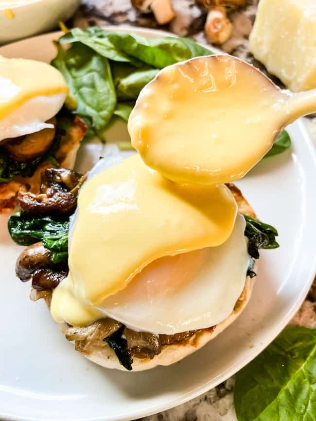 Parmesan Hollandaise being poured on an Eggs Florentine Benedict stack