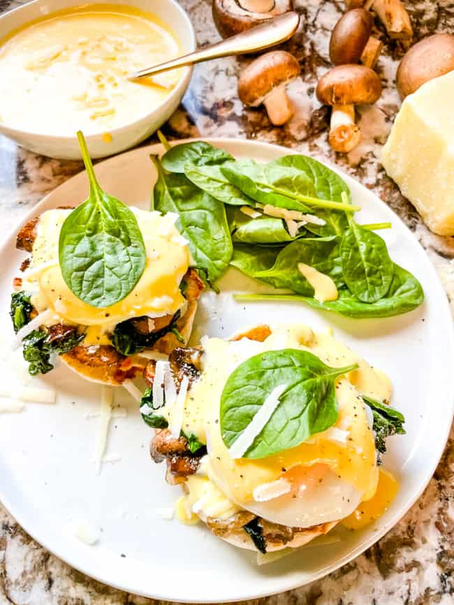 Two stacks of Eggs Florentine Benedict from the top on a white round plate