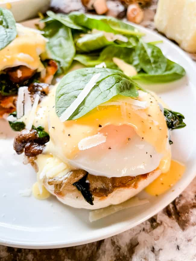 Close up of a stack of Eggs Florentine Benedict on a white plate