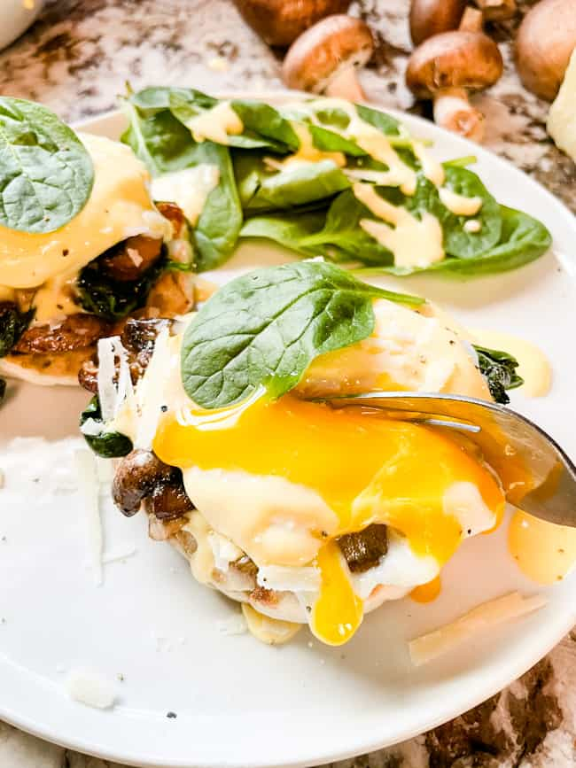 A fork breaking an egg stack open with the yolk running down the benedict