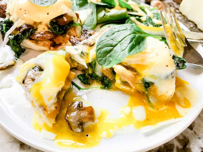 An Eggs Florentine Benedict stack cut open on a white plate