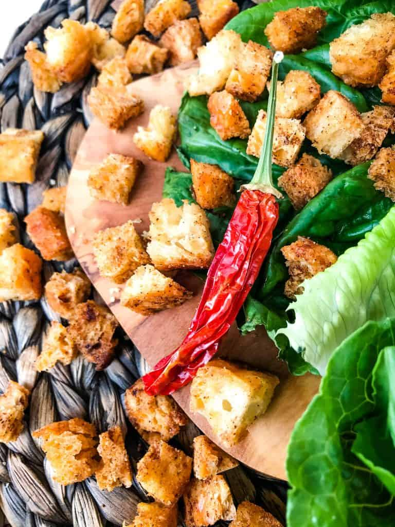 Croutons scattered on a board with a pepper