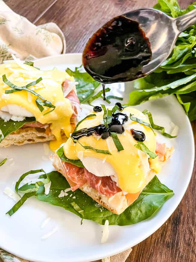 A spoon pouring balsamic glaze on a stack of Italian Prosciutto Eggs Benedict
