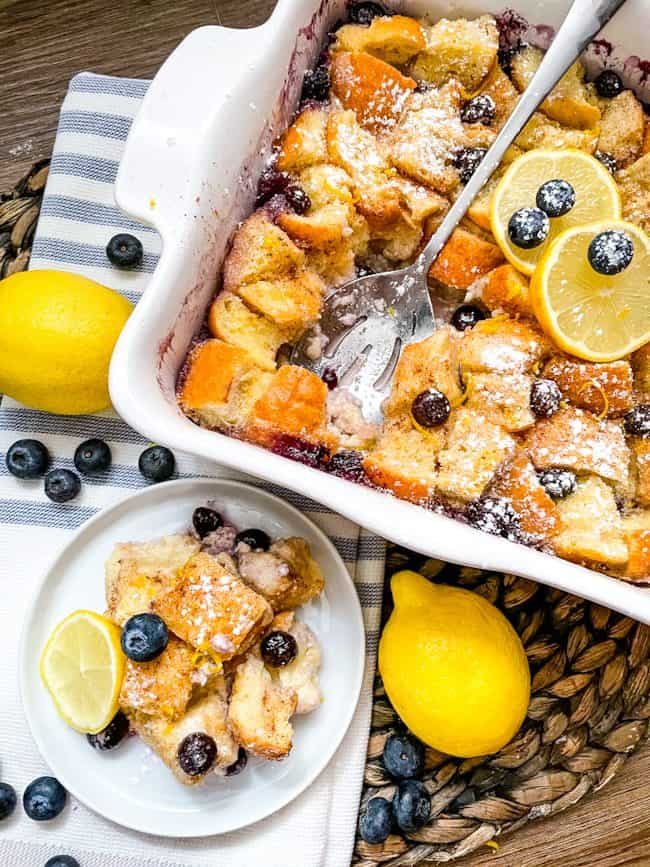 A dish of Lemon Blueberry Bread Pudding with a plate of it next to it