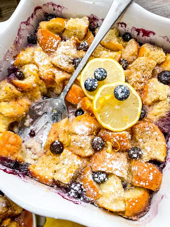 A white dish full of Lemon Blueberry Bread Pudding with a spoon in it