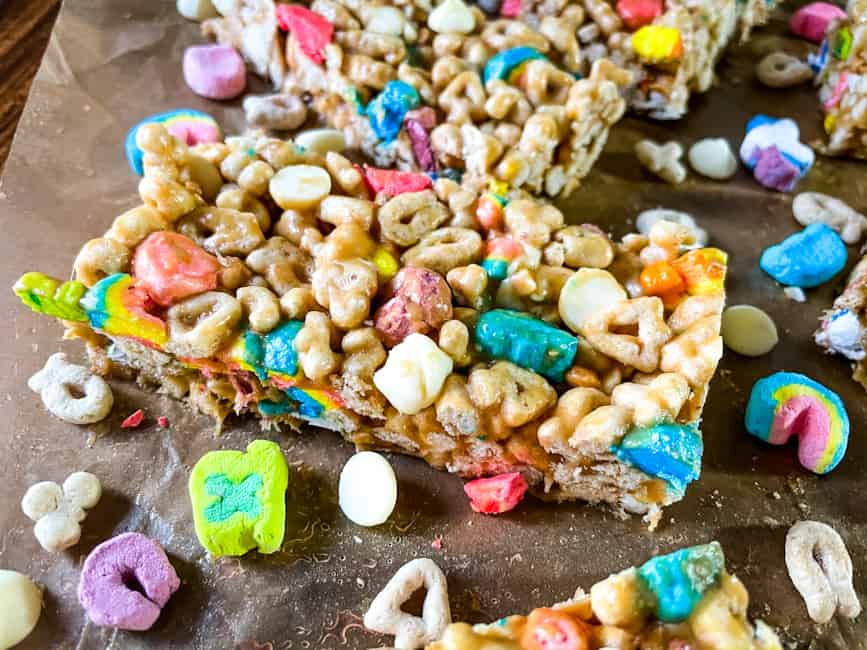 Close up of a Lucky Charms Cereal Bar surrounded by cereal pieces