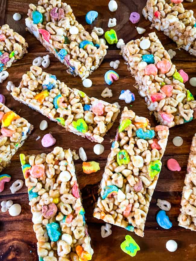 Lucky Charms Cereal Bars scattered on a wood surface with marshmallows and cereal around them