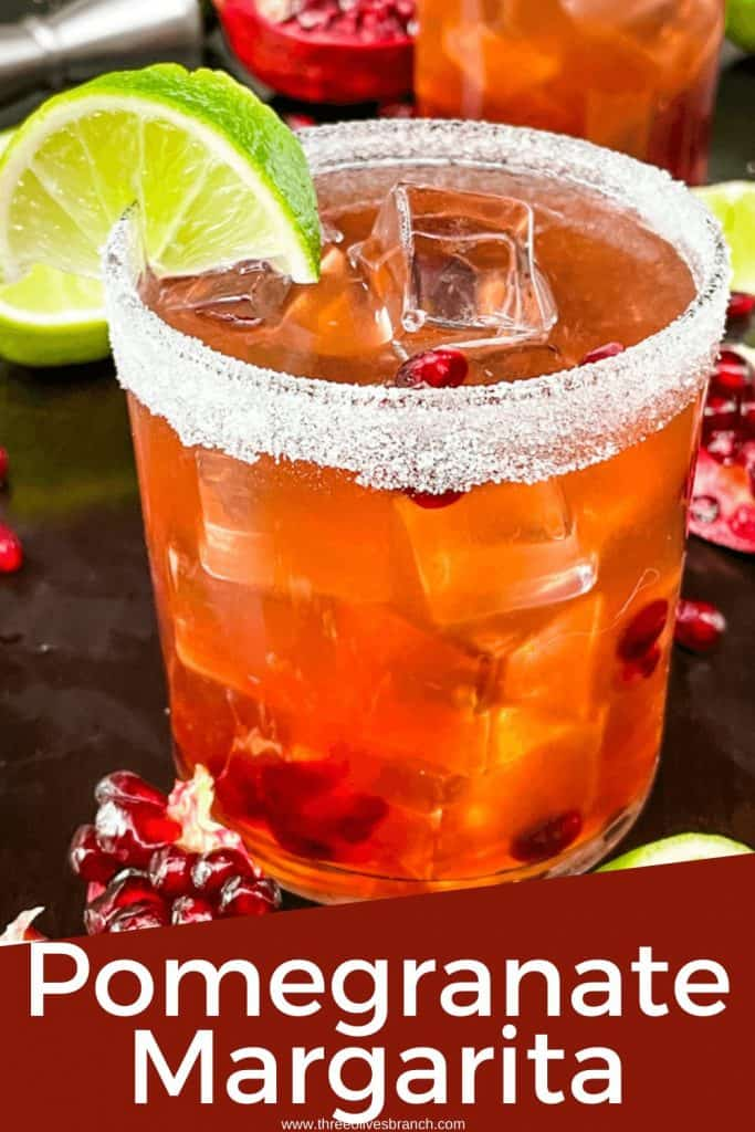 Pin image for Pomegranate Margarita with a short glass filled with the red tequila cocktail, a sugar rim, and a lime wedge with title at bottom
