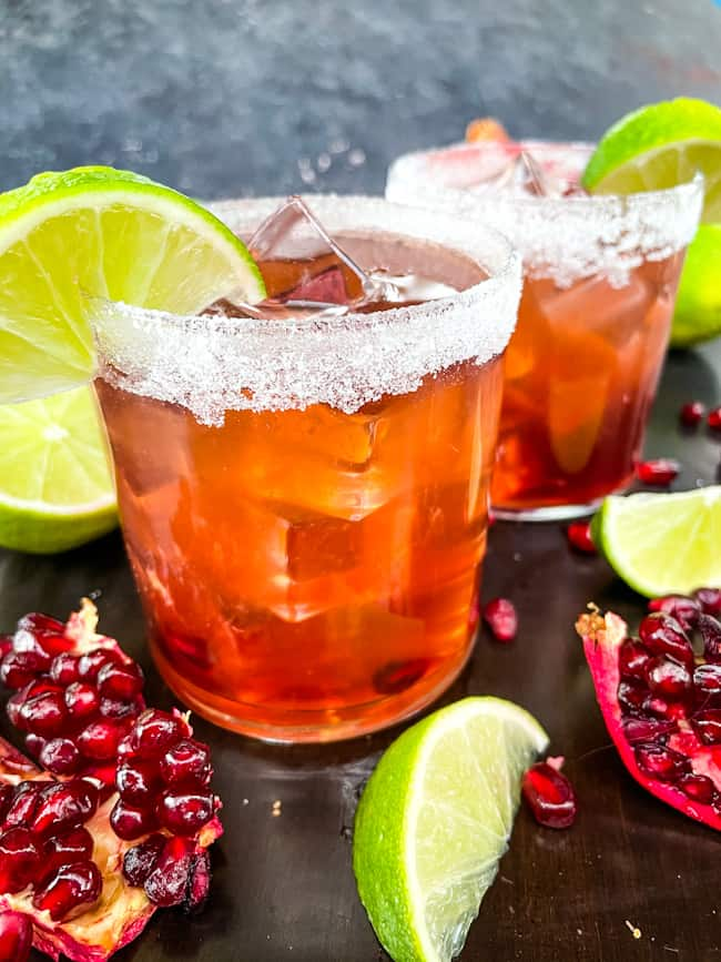 Two cocktails surrounded by limes and pomegranate pieces and seeds