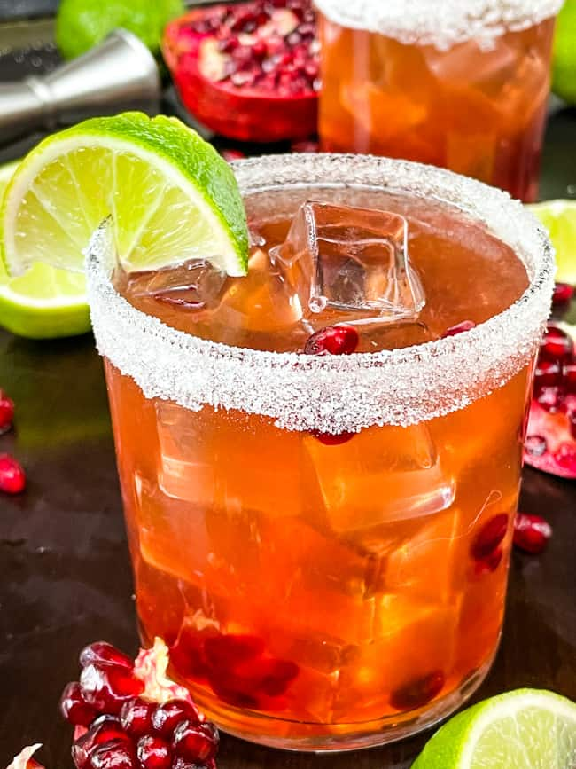 Close up of a Pomegranate Margarita in a short glass with a sugar rim and lime wedge