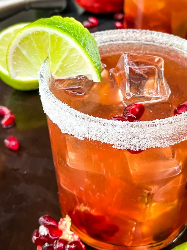 A close up of a Pomegranate Margarita in a short glass with a lime wedge