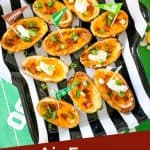 Classic filled Air Fryer Potato Skins with cheddar, bacon, chives, and sour cream on a football tray with title at bottom