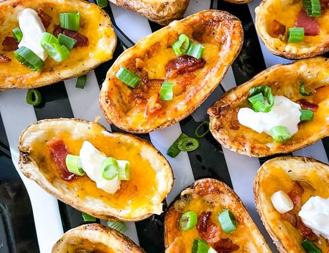 Air Fryer Potato Skins filled with bacon, cheese, sour cream, and chives