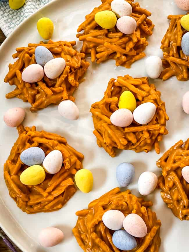 Several Birds Nest Cookies on a white plate with mini eggs in and around the nests