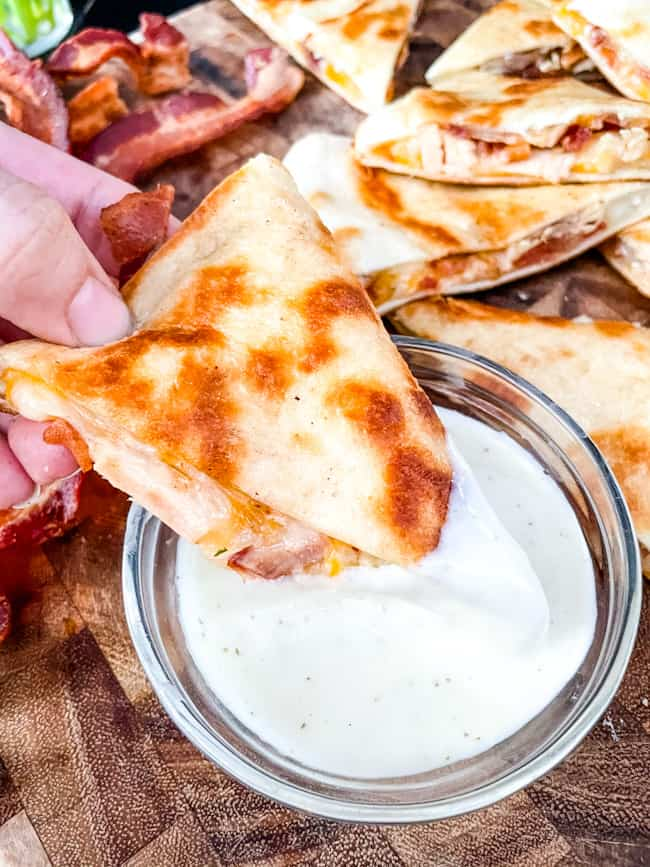 Chicken Bacon Ranch Quesadilla being dunked into ranch