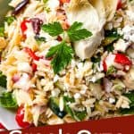 Pin image of Greek Orzo Salad in a bowl with artichoke heart on top and title at bottom