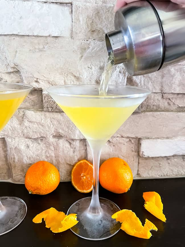 A Orange Martini being poured into a frosted glass