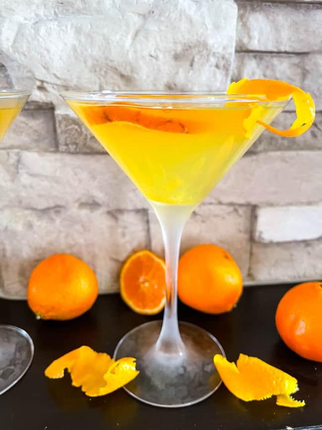 An Orange Martini with oranges around it