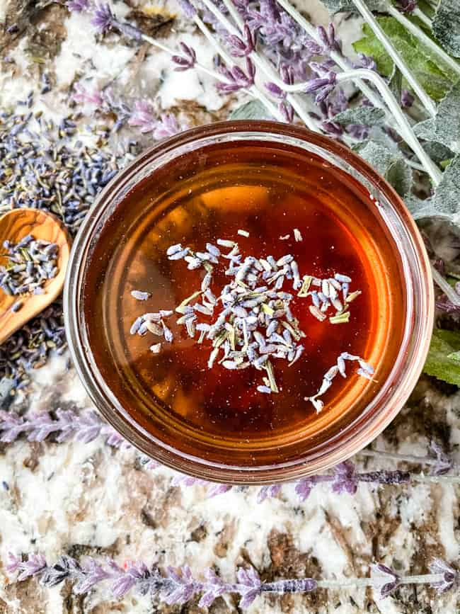 Top view of a bowl of Lavender Syrup Recipe with some lavender on top and around it