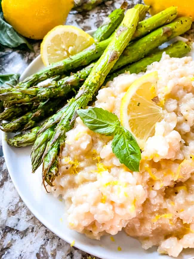 A round white plate with Risotto al Limone (Lemon Risotto) and asparagus